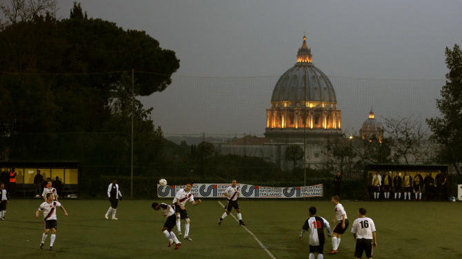 "Players of Collegio San Paolo and North American Martyrs teams play their Clericus Cup soccer match, in Rome, Sunday, March 10, 2013. Vatican-supported soccer league matches went ahead as scheduled Sunday on a hill overlooking St. Peter's Basilica, shown in background. For the teams of seminaries, missionaries and oratories, however, the pre- and post-game talk centered on the coming conclave to elect a new pope. A coach of a Brazilian team was absent because he was chosen to drive two cardinals to Assisi for the day. ""It didn't go so well today,"" Aldemir Fracisco Belever, the captain of the Collegio Pio Brasiliano seminary said after a 4-1 loss to Redemptoris Mater, a team featuring seminarians and priests with the Mater neocatechumenal movement. ""It wasn't easy without our coach."" (AP Photo/Alessandra Tarantino)"
