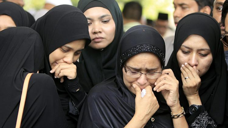 Family members of Nur Shazana, a Malaysia Airlines crew member who was among the victims onboard Flight MH17, cry during a burial ceremony at Taman Selatan Muslim cemetery in Putrajaya, Malaysia, Friday, Aug. 22, 2014. Carried by soldiers and draped in the national flag, coffins carrying Malaysian victims of Flight MH17 returned home Friday to a country still searching for those onboard another doomed jet and a government battling the political fallout of the twin tragedies. (AP Photo/Lai Seng Sin)