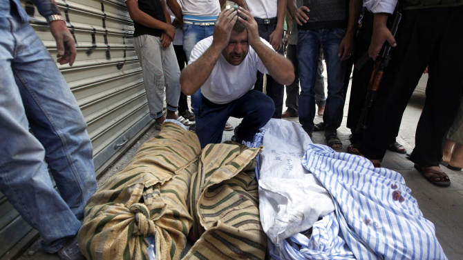 A Syrian man grieves over the bodies of four members of his family, who were killed when an airstrike hit their house, as they lie on the side of the street outside a field hospital in Aleppo, Syria, Friday, Aug. 17, 2012. Rebel footholds in Aleppo have been the target of weeks of Syrian shelling and air attacks as part of wider offensives by President Bashar Assad's regime. Rebels have been driven from some areas, but the report of clashes near the airport suggests the battles could be shifting to new fronts.(AP Photo/ Khalil Hamra)