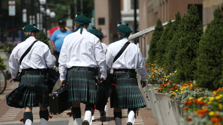Members of the New Haven Connecticut Fire Department Emerald Society bag pipers walk down a sidewalk in downtown New Haven