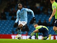Manchester City's Mario Balotelli (L) slips past Aston Villa's Karim El Ahmadi (C) during their League Cup match on September 25. City took the lead with Balotelli's first goal of the season but saw Gareth Barry's own-goal pull Villa level