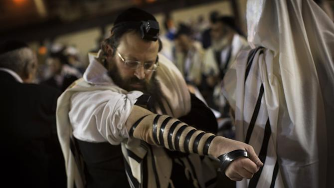 An Ultra-Orthodox Jew adjusts a Tefillin, also known as phylacteries, during a prayer at the Western Wall in Jerusalem's Old City, before the start the holiday of Rosh Hashana, early Sunday, Sept. 16, 2012. Jews will mark the holiday of Rosh Hashana, or the Jewish New Year at sundown Sunday. (AP Photo/Bernat Armangue)