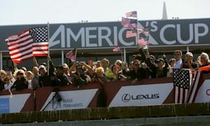Fans of Oracle Team USA cheer after their team defeated Emirates Team New Zealand during Race 18 of the 34th America's Cup yacht sailing race in San Francisco, California