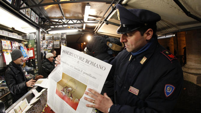 A policeman hold the Osservatore Romano newspaper in Rome
