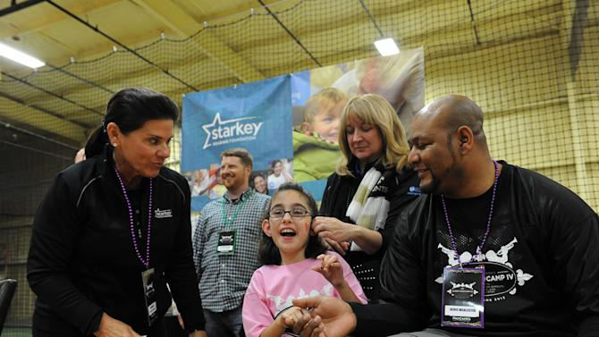 Starkey Hearing Foundation co-founder Tani Austin, left,  looks on as nine-year-old Maci Rowen is comforted by former Saints player Deuce McAllister while getting  fitted for a hearing aid at The Citi Garth Brooks Super Pro Camp on Friday, Feb. 1, 2013 in New Orleans. (Photo by Cheryl Gerber/Invision for Starkey Hearing Foundation/AP Images)