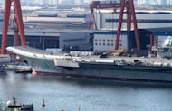 China's first aircraft carrier is berthed at Dalian port on September 5. China's first aircraft carrier has been handed over to the navy of the People's Liberation Army, state press said, amid rising tensions over disputed waters in the East and South China Seas.