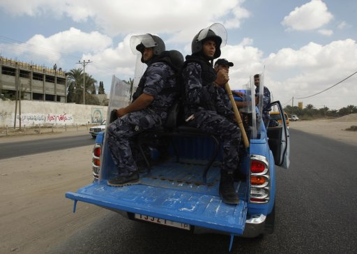 Hamas policemen ride a pick-up truck in the central Gaza Strip