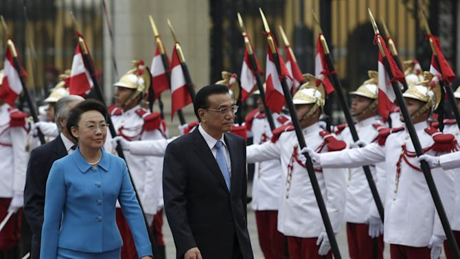 Chinese Premier Li Keqiang and his wife Cheng Hong walk past an honour guard upon their arrival to the government palace in Lima