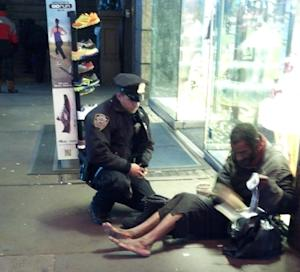 FILE- This file photo provided by Jennifer Foster from Nov. 14, 2012, shows New York City Police Officer Larry DePrimo presenting a barefoot homeless man in New York's Time Square with boots .  (AP Photo/Jennifer Foster, File)