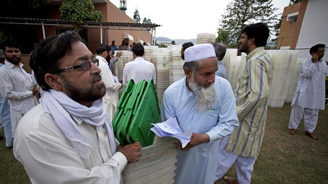 Pakistani election staff carry ballot boxes for tomorrow;s elections in Islamabad, Pakistan, Friday, May 10, 2013. An especially violent spate of killings, kidnappings and bombings marred the run-up to Pakistan's nationwide election, capped Thursday by the abduction of the son of a former prime minister as he was rallying supporters on the last day of campaigning before the historic vote. (AP Photo/B.K. Bangash)
