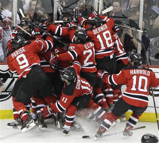The New Jersey Devils celebrate after beating the New York Rangers 3-2 in overtime of Game 6 of the NHL hockey Stanley Cup Eastern Conference finals Friday, May 25, 2012, in Newark, N.J. The Devils advanced to the Stanley Cup finals. (AP Photo/Frank Franklin II)