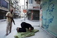 A Syrian rebel stands guard next to a comrade praying during a short break of heavy fighting in the Salaheddin district of Aleppo on August 3. Syria&#39;s prime minister Riad Hijab has joined the anti-regime revolt and fled abroad, in what Washington and the opposition hailed as a major blow to President Bashar al-Assad