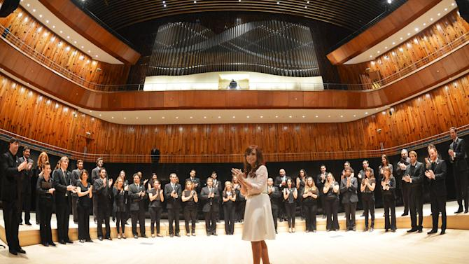 Argentina's President Fernandez de Kirchner applauds in front of musicians from Argentina's National Symphony Orchestra in the 'Blue Whale' auditorium during the official inauguration of the Kirchner Cultural Center in Buenos Aires