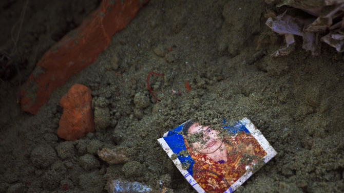 """A photo of a missing garment worker is partially buried in soil at the site of the garment factory building collapse in Savar, near Dhaka, Bangladesh, Saturday, May 5, 2013. The death toll in the accident rose to more than 530 on Saturday, a day after the country's finance minister downplayed the impact of the disaster on the garment industry, saying he didn't think it was """"really serious."""" (AP Photo/Ismail Ferdous)"""