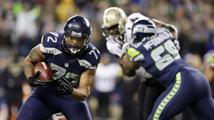 In this Dec. 2, 2013, file photo, Seattle Seahawks' defensive end Michael Bennett (72) returns a fumble for a touchdown during an NFL football game against the New Orleans Saints in Seattle. The Seahawks announced Monday, March 10, 2014, that free-agent Bennett had signed a multi-year deal with the team