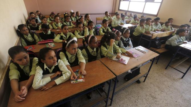 Students attend at a class on the first day of their new school year at a government school in Giza