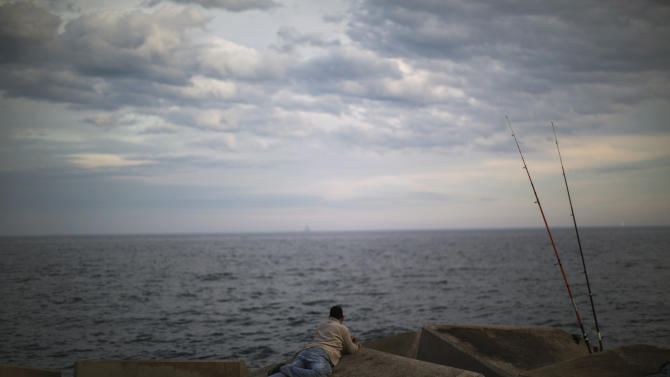 AP10ThingsToSee - A man watches the Mediterranean sea near his fishing rods at the port of Barcelona, Spain, Tuesday, May 7, 2013. (AP Photo/Emilio Morenatti, File)