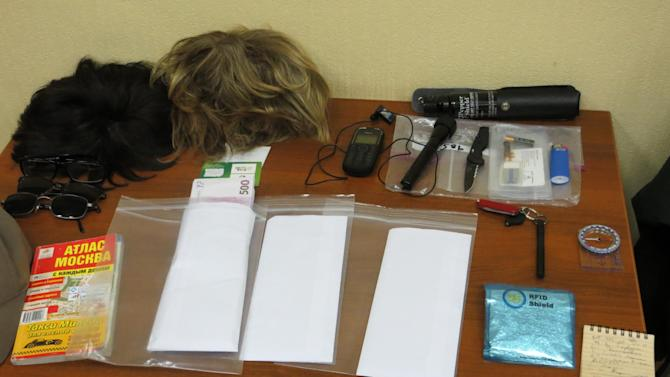 In this handout photo  provided by the FSB, acronym for Russian Federal Security Service, wigs and spying gadgets carried by a man claimed by FSB to be Ryan Fogle, a third secretary at the U.S. Embassy in Moscow, when he was detained, are shown in the FSB offices in Moscow, early Tuesday, May 14, 2013. Russia's security services say they have caught a U.S. diplomat who they claim is a CIA agent in a red-handed attempt to recruit a Russian agent. Ryan Fogle, a third secretary at the U.S. Embassy in Moscow, was carrying special technical equipment, disguises, written instructions and a large sum of money when he was detained overnight, the FSB said in a statement Tuesday. Fogle was handed over to U.S. embassy officials, the FSB,  said. (AP Photo/FSB Public Relations Center)