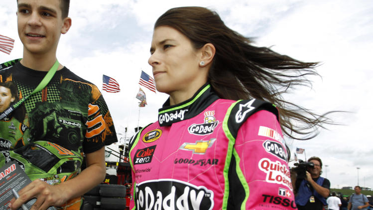 Driver Danica Patrick walks through the garage area before practicing for Sunday's NASCAR Sprint Cup series auto race at Kansas Speedway in Kansas City, Kan., Friday, Oct. 4, 2013. (AP Photo/Colin E. Braley)