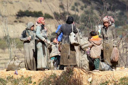 Internally displaced people, covered with mud, wait as they are stuck in the town of Khirbet Al-Joz, in Latakia countryside, waiting to get permission to cross into Turkey near the Syrian-Turkish border
