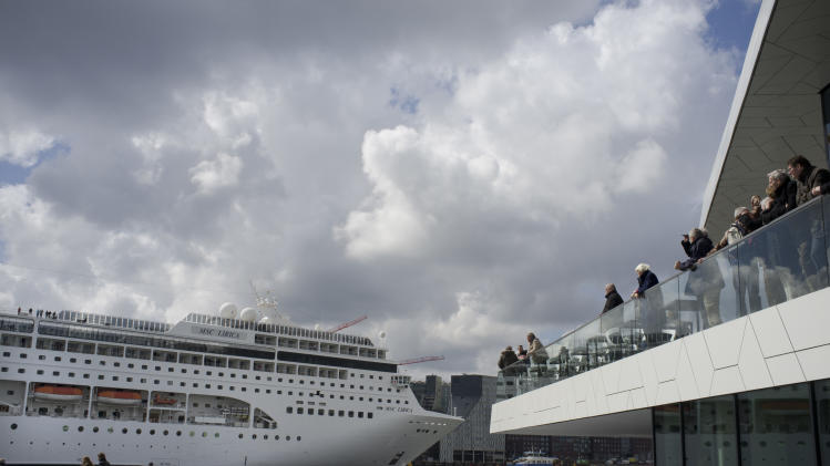 FILE - This April 21, 2012 file photo shows people visiting the new EYE Film Instute take pictures of the MSC Lirica, a Panama-registered cruise ship passing on IJ river in Amsterdam, Netherlands. One of Amsterdam's newest landmarks is a stark, white film institute, called the EYE, perched on northern bank of the IJ waterway. While you have to pay to take in a movie, the cafe and its terrace are open to all who are prepared to buy a cup of coffee or light meal and offer a front-row seat to watch barges chug along the IJ against a backdrop of the city skyline. (AP Photo/Peter Dejong)