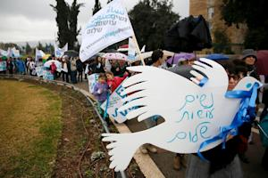 Israeli women hold placards and flags during a march…