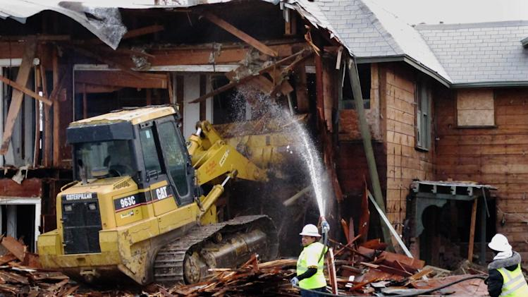 A bulldozer is used to demolish a two-story apartment building  in Dallas, Texas on Monday, January 14, 2013 where Lee Harvey Oswald briefly lived before assassinating President John F. Kennedy. The rundown building was demolished by court order after a dispute between the city and landlord Jane Bryant. (AP Photo/Nomaan Merchant)