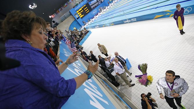 United States' Michael Phelps throws flowers to his mother Debbie after the men's 4 X 100-meter medley relay at the Aquatics Centre in the Olympic Park during the 2012 Summer Olympics, London, Saturday, Aug. 4, 2012. (AP Photo/Jae C. Hong)