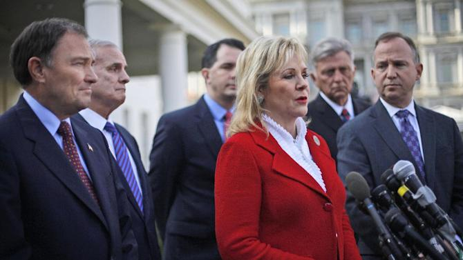 National Governors Association (NGA) Vice Chair, Oklahoma Gov. Mary Fallin, center, talks to reporters outside the White House in Washington, Tuesday, Dec. 4, 2012, following a meeting between the NGA executive committee and President Barack Obama regarding the fiscal cliff. From left are, Utah Gov. Gary Herbert, Minnesota Gov. Mark Dayton, Wisconsin Gov. Scott Walker, Fallin, Arkansas Gov. Mike Beebe, and NGA Chairman, Delaware Gov. Jack Markell. (AP Photo/Pablo Martinez Monsivais)