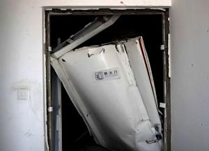A broken fireproof door is pictured inside a building, …
