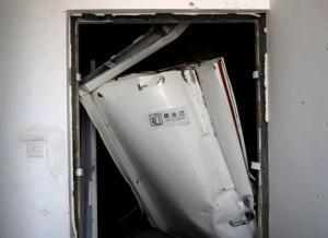 A broken fireproof door is pictured inside a building,…