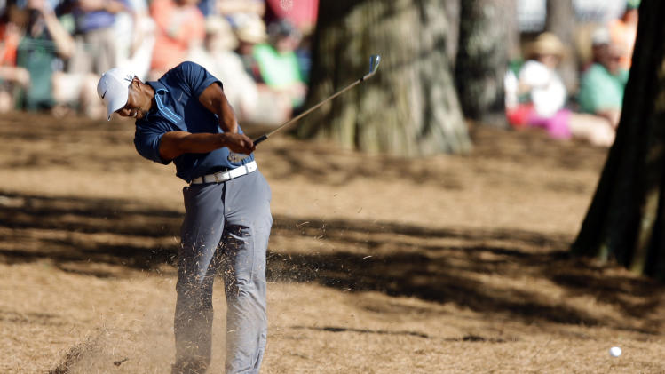 Tiger Woods hits out of the rough off the 15th fairway during the third round of the Masters golf tournament Saturday, April 13, 2013, in Augusta, Ga. (AP Photo/Matt Slocum)