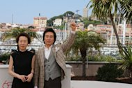 "South Korean actor Baek Yoon-sik (R) raises his fist while posing with South Korean actress Youn Yuh-jung during the photocall of ""Do-Nui Mat"" (The Taste of Money) presented in competition at the 65th Cannes film festival. A sex-infused expose of rampant corruption among the super-rich in today's South Korea premiered, but the director slammed the Western view of Asian cinema"