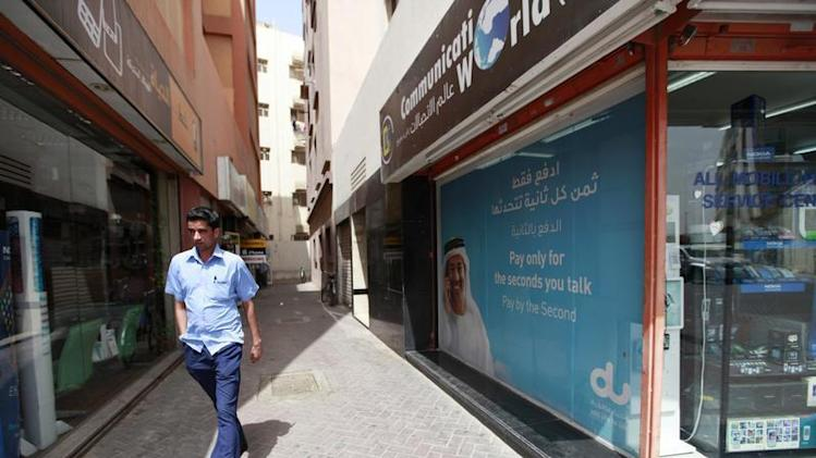 A man walks past a Du telecommunications advertisement in Deira in Dubai