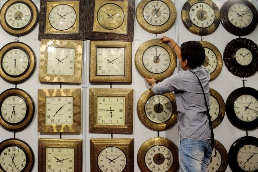 <p>Indian exhibitor Hardik arranges a display of wooden clocks at a stall during an 'Interior and Lifestyle' exhibition in Amritsar on September 7, 2012. The Indian public's confidence in their economy and government has plunged in the last year, according to a US study published as the country battles galloping inflation and slowing growth.</p>