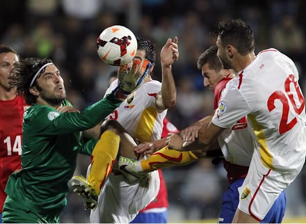 Serbia's goalkeeper Vladimir Stojkovic, left , challenges for the ball with Macedonia's Boban Grncarov, center and Jovan Kostovski during their World Cup 2014 Group A qualifying soccer match at the Ci