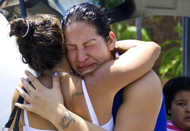 Lupe Diaz, right, sister of Manuel Diaz, gets a hug from Theresa Smith during a protest in front of the Anaheim Police Department, Sunday, July 22, 2012, in Anaheim, Calif. Manuel Diaz, an allegedly unarmed man, was shot by Anaheim Police on Saturday, The Orange County Register reports. Smith said her son was also killed by police two years ago. (AP Photo/The Orange County Register, Mindy Schauer) MAGS OUT; LOS ANGELES TIMES OUT.