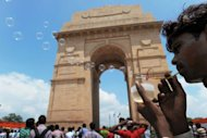 <p>A street vendor blows soap bubbles at the India Gate monument in New Delhi on August 15, 2012. A modern market economy cannot function without a modicum of altruism and trustworthiness, according to Kaushik Basu, former government's chief economic advisor.</p>