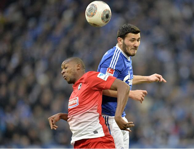 Schalke's Sead Kolasinac, up, and Freiburg's Karim Guede of Slovakia challenge for the ball during the German Bundesliga soccer match between FC Schalke 04 and SC Freiburg in Gelsenkirchen, Ge