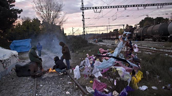 Stranded migrants gather around fire to shelter from the early morning cold at the Greek-Macedonian border, near the northern Greek village of Idomeni, Sunday, Nov. 29, 2015. (AP Photo/Muhammed Muheisen)