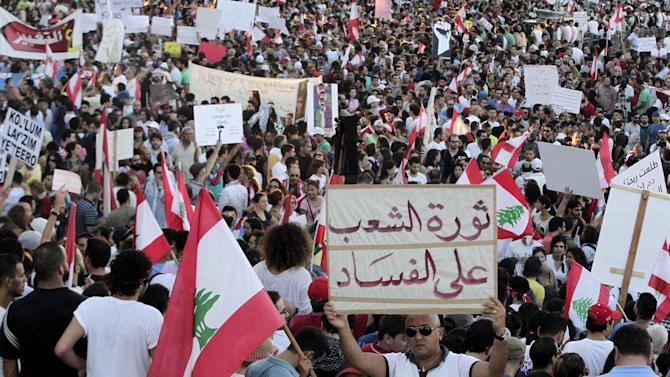 "A Lebanese anti-government protester holds an Arabic placard that reads, ""The people revolution against corruption,"" during a demonstration in Martyrs' Square, downtown Beirut, Lebanon, Saturday, Aug. 29, 2015. Thousands of people staged the largest of the demonstrations that began last week over garbage piling up in the streets of Beirut following the closure of a main landfill. The government's failure to resolve the crisis has evolved into wider protests against a political class that has dominated Lebanon since the end of the country's civil war in 1990 and a government that has failed to provide even basic services to the people. (AP Photo/Bilal Hussein)"