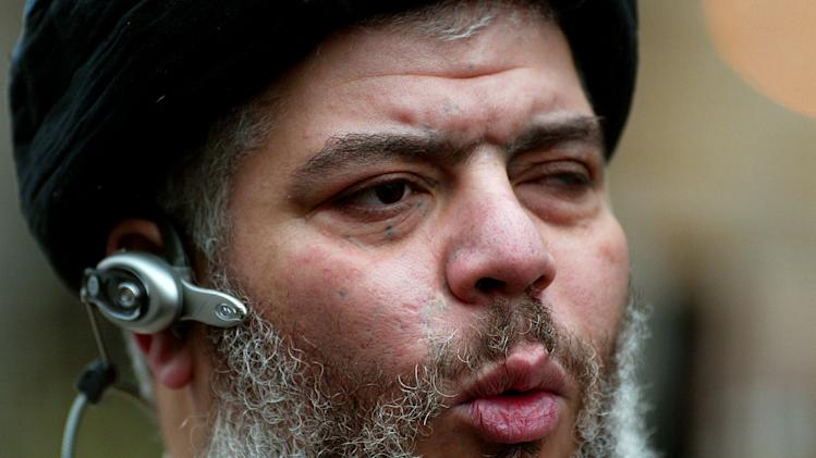 FILE - In this Jan. 23, 2004 file photo, self-styled cleric Abu Hamza al-Masri leads his followers in prayer in a street outside Finsbury Park Mosque, on the first anniversary of its closure by anti-terrorism police, London. Britain is set to extradite its most recognizable extremist, Abu Hamza al-Masri, to the United States, sending a national hate figure to face charges of helping set up a terrorist training camp in rural Oregon. Britain's Home Office said Monday Sept. 24, 2012 that radical Muslim cleric Abu Hamza al-Masri has lost an appeal regarding his extradition to the United States.(AP Photo/John D McHugh, File)