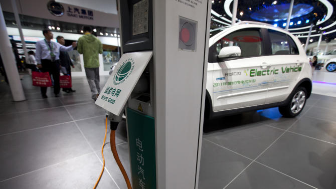 A charging station for electric vehicles is displayed together with the Great Wall C20 EV, an electric compact crossover produced by Great Wall Motors Company, at the Beijing International Automotive Exhibition in Beijing, China, Tuesday, April 24, 2012.  China's leaders are finding it's a lot tougher to create a world-beating electric car industry than they hoped.  In 2009, they announced bold plans to cash in on demand for clean vehicles by making China a global power in electric car manufacturing. They pledged billions of dollars for research and called for annual sales of 500,000 cars by 2015.  Today, Beijing is scaling back its ambitions, chastened by technological hurdles and lack of buyer interest. Developers have yet to achieve breakthroughs and will be lucky to sell 2,000 cars this year, mostly taxis.  (AP Photo/Alexander F. Yuan)