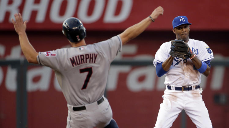 Kansas City Royals shortstop Alcides Escobar, right, throws to first too late for the double play on a fielder's choice hit into by Cleveland Indians' Jose Ramirez after forcing out Indians' David Murphy (7) at second during the fourth inning of a baseball game on Friday, July 25, 2014, in Kansas City, Mo. (AP Photo/Charlie Riedel)
