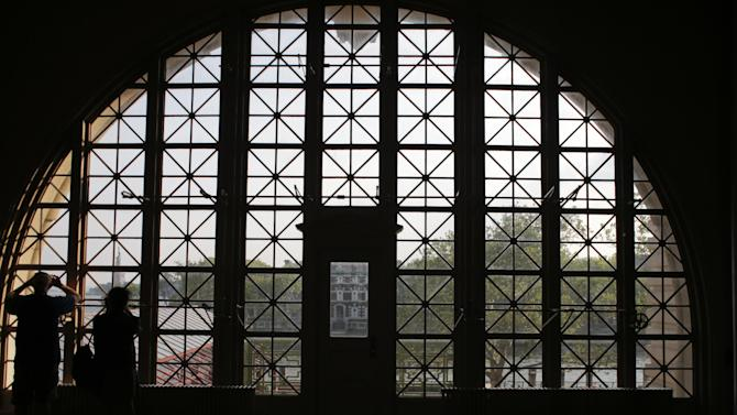 Tourists photograph the Statue of Liberty from the Reistry Room at Ellis Island Wednesday, July 29, 2015, in Ellis Island.  (AP Photo/Frank Franklin II)