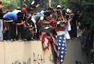 <p>Egyptian protesters tear down the US flag at the US embassy in Cairo on September 11. The American ambassador to Libya, J. Christopher Stevens, and three officials were killed when a mob attacked the US consulate in the eastern city of Benghazi, the interior ministry said Wednesday, just hours after Islamists also stormed Washington's embassy in Cairo.</p>