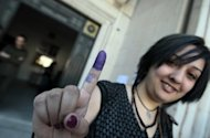 "A Syrian woman shows her ink-stained finger after casting her vote at a polling station in Damascus. Syrians voted on Monday in the country's first ""multiparty"" parliamentary election in five decades, held against a backdrop of violence and dismissed as a sham by the opposition"