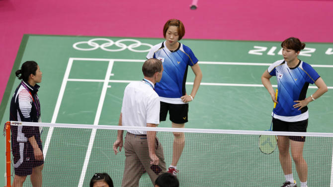 Tournament referee Torsten Berg speaks to players from South Korea and Indonesia during their women's doubles group play stage Group C badminton match during the London 2012 Olympic Games at the Wembley Arena