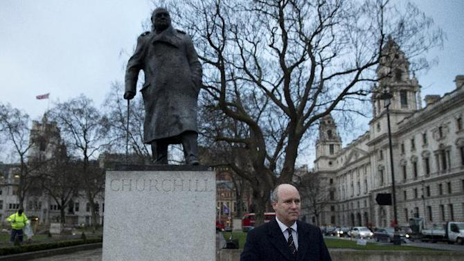 Randolph Churchill, the great-grandson of the former British World War II wartime Prime Minister Winston Churchill, talks to the media after laying flowers at the foot of his statue in Parliament Square in London Friday, Jan. 30, 2015. The 50th anniversary of the late prime minister's state funeral falls on Friday with a number of events in London to commemorate it. Churchill died on Jan. 24, 1965 at the age of 90. (AP Photo/Alastair Grant)