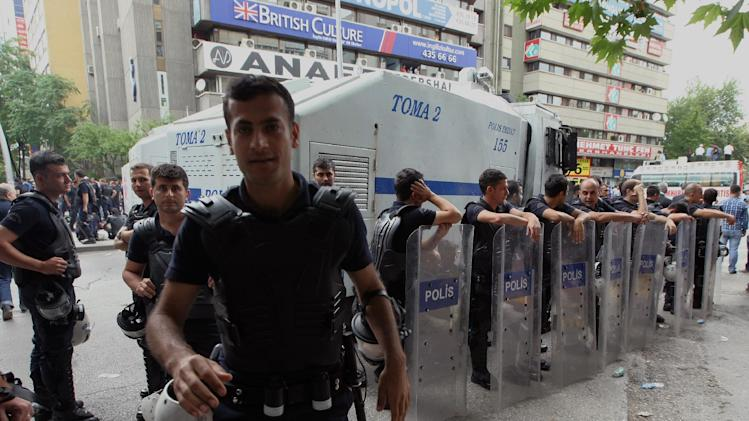 A police officer reacts to cameras as others stand during a rally by the labor unions in Ankara, Turkey, Monday, June 17, 2013. A day earlier, riot police cordoned off streets, set up roadblocks and fired tear gas and water cannons to prevent anti-government protesters from an effort to return to Taksim Square in Istanbul. Labor unions and political foes of Prime Minister Recep Erdogan rallied Monday by the thousands across Turkey, hoping to capitalize on weeks of protest that began as small-scale activism and parlay it into a chance to register broader discontent.(AP Photo/Burhan Ozbilici)